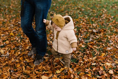 Child in Beige Hoodie and Brown Denim Jeans Standing on Dried Leaves