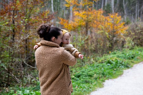 Woman in Brown Sweater Carrying Baby in Brown Sweater
