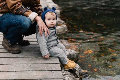 Photo Of Toddler Sitting On Wooden Dock