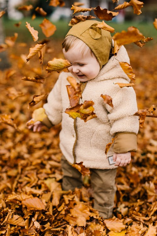 Photo Of Baby Playing With Dried Leaves