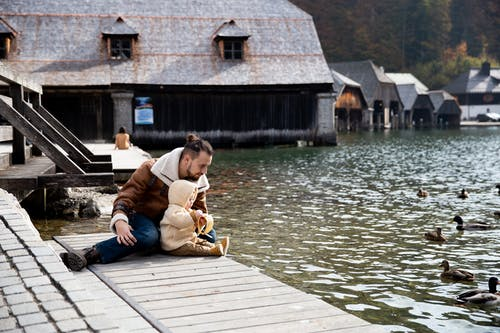 Photo Of Man And Baby Sitting On Wooden Dock