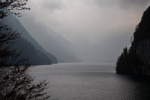 Breathtaking view of mountainous terrain with lake in cloudy day