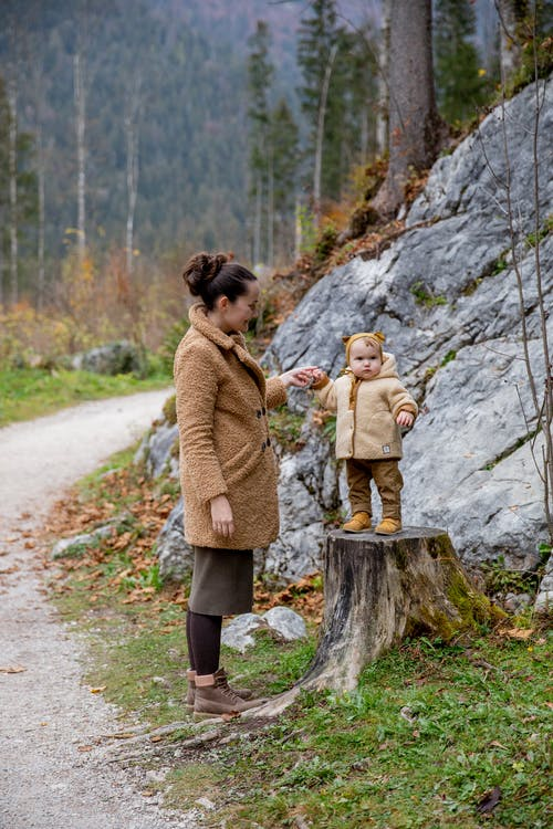 Photo Of Baby Standing On Tree Log