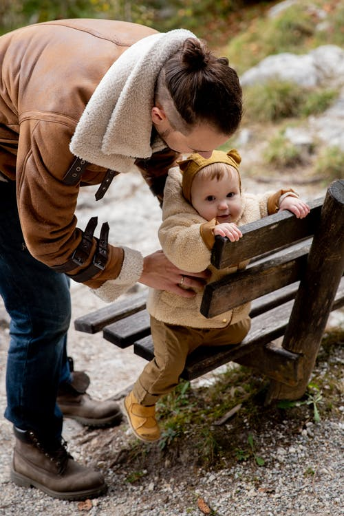 Photo Of Baby Holding On Wooden Bench
