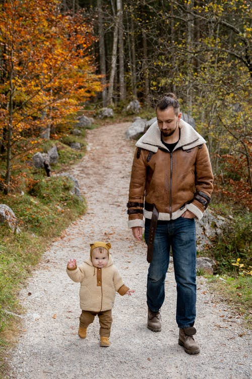Photo Of Man Walking Beside Child