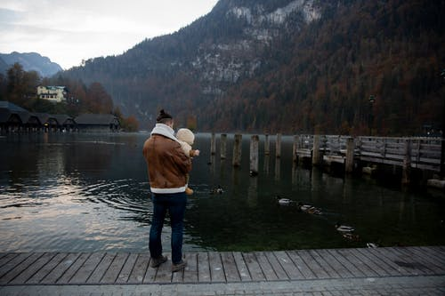 Photo Of Man Carrying Baby Standing On Wooden Dock