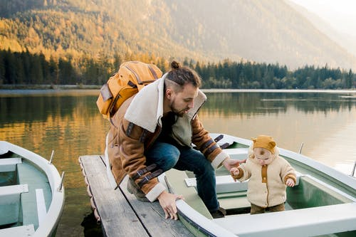 Father with little kid standing on boat on wooden pier near lake in mountains