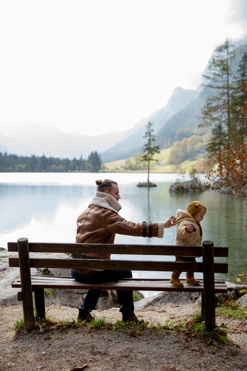 Father and girl on bench on lake shore