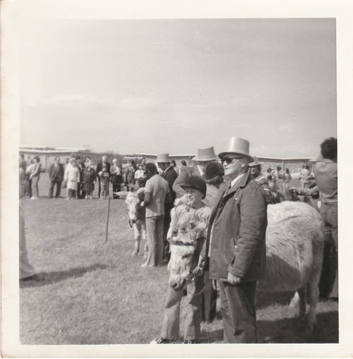 Grayscale Photo of Man in Jacket Standing Beside Sheep