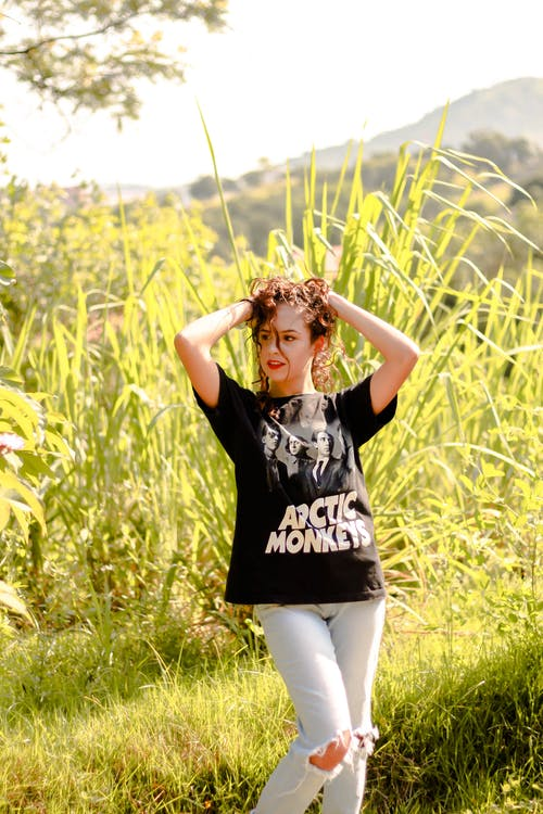 Woman in Black and White T-shirt and Tattered Pants Standing on Green Grass Field