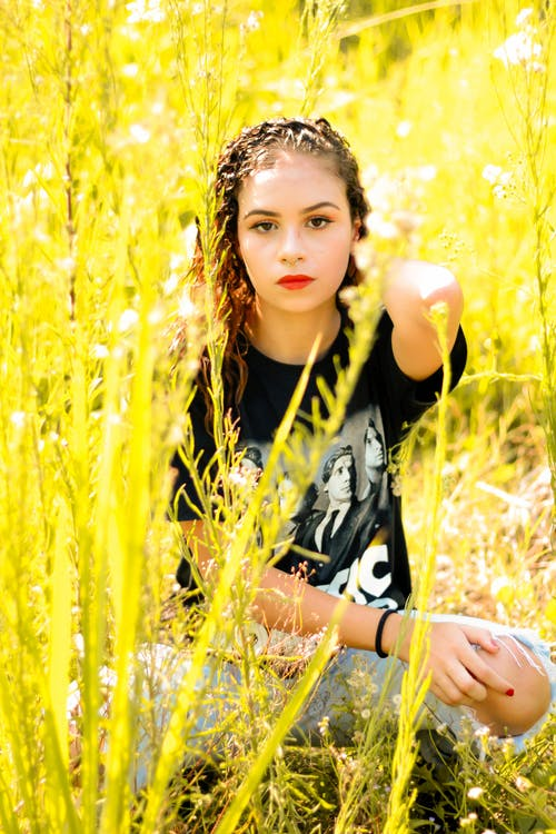 Woman in Black and White Shirt Sitting on Yellow Grass Field