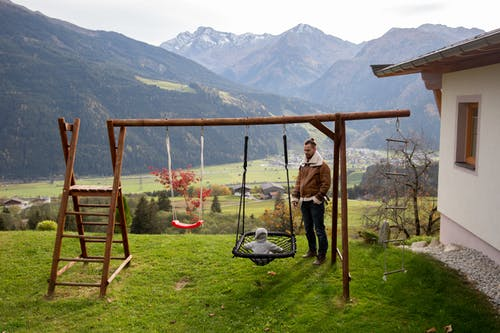 Brown Wooden Swing on Green Grass Field Near Mountains