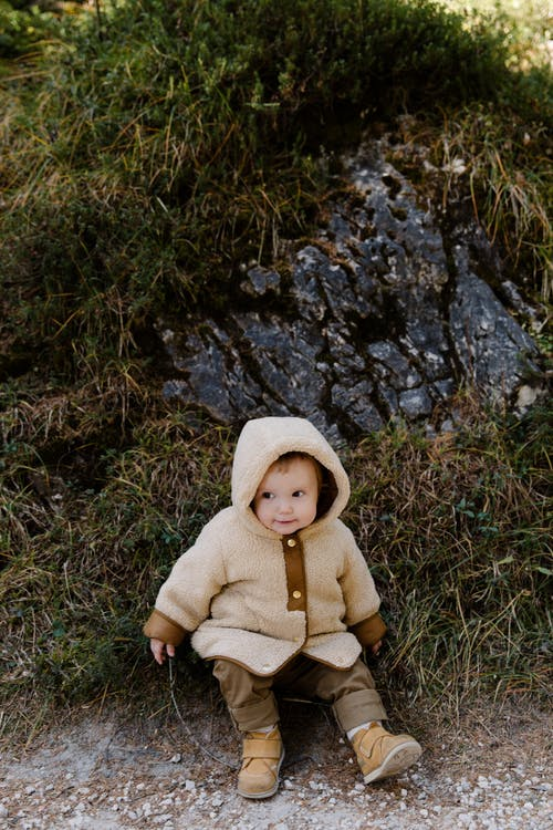 Child in Brown Hoodie Sitting on Green Grass Field