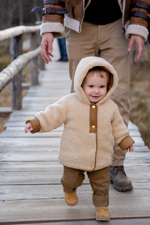 Child in Brown Jacket and Brown Pants Walking on Wooden Bridge
