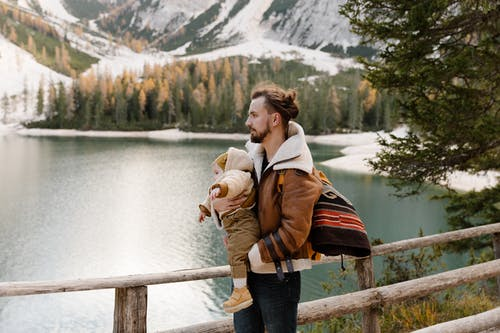 Man in Brown Jacket Carrying His Baby