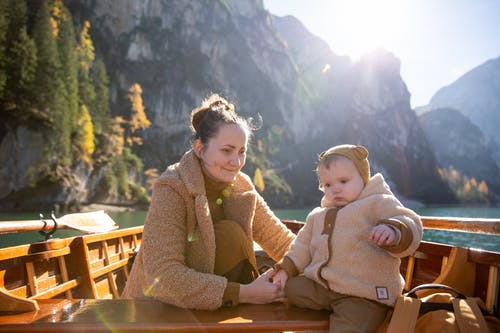 Woman in Brown Sweater Sitting on Brown Wooden Boat With Baby in Brown Sweater