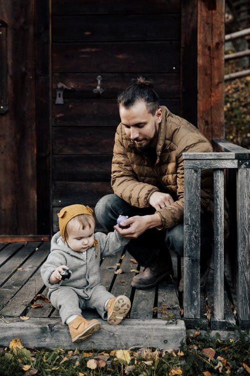 Man in Brown Jacket and Blue Denim Jeans Sitting  Holding His Child