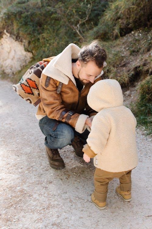 Man in Brown Jacket with His Child Wearing Brown Hoodie