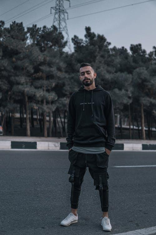 Man in Black Hoodie Standing on Road