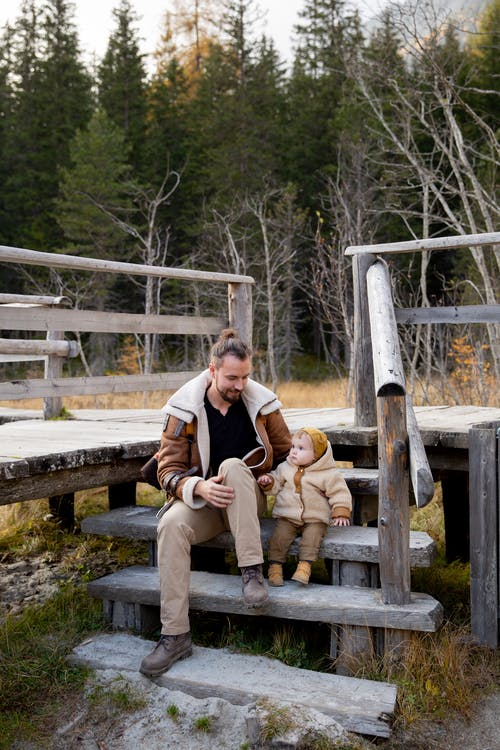 Photo Of Man And Baby Sitting on Wooden Stairs