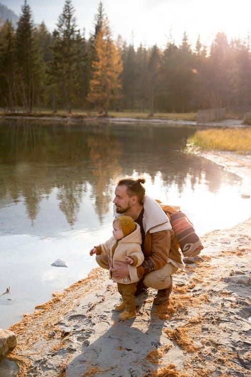 Man in Brown Jacket Sitting on Rock Near Lake