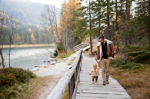 Photo Of Man And Baby Walking On Wooden Walkway