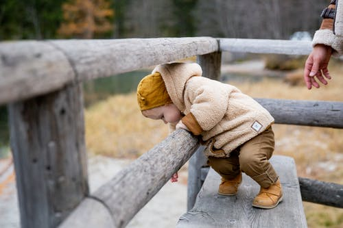 Photo Of baby Leaning On Wooden Fence
