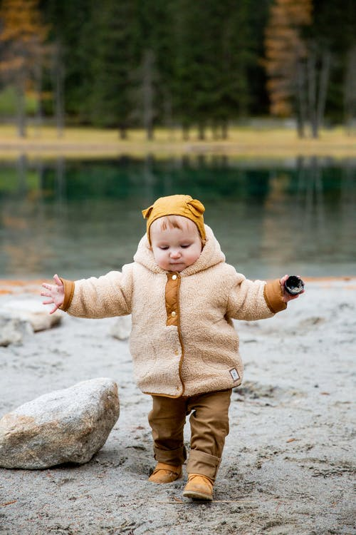 Child in Brown Jacket and Yellow Knit Cap Standing on Sand Near Big Rock