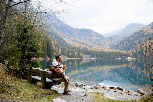 Man Sitting on Bench Near Lake