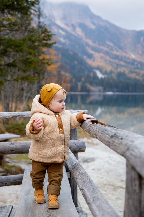 Child in Brown Jacket Standing on Wooden Fence Near Lake