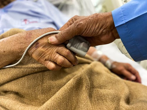 Old couple holding hands in hospital