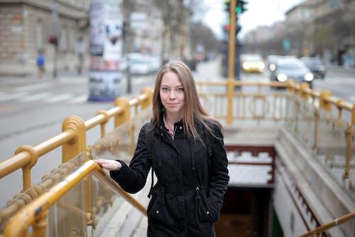 Woman in Black Leather Jacket Standing Beside Yellow Metal Railings