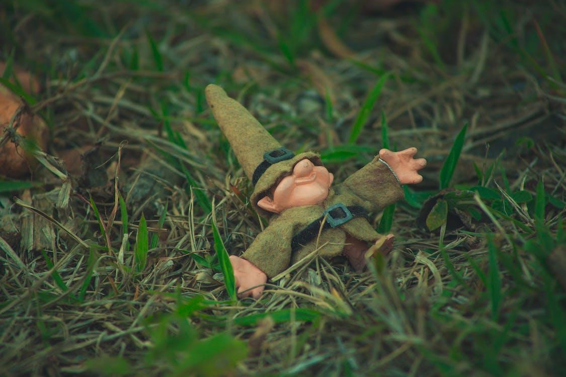 Little dwarf doll lying in grass