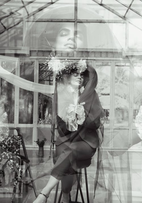Black and white of content ethnic stylish female with closed eyes in trendy outfit sitting near entrance in modern building