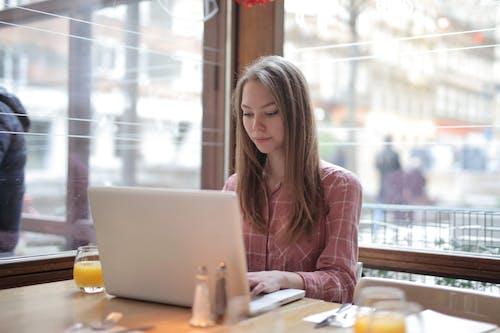Woman in Pink Shirt Using Laptop
