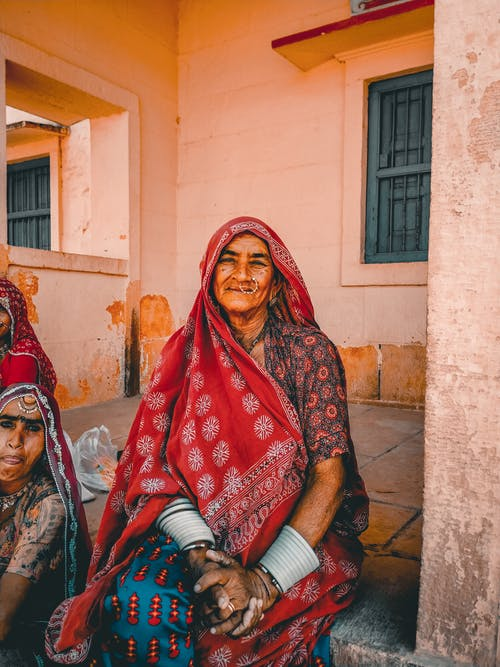 Old Indian woman with girl sitting on terrace