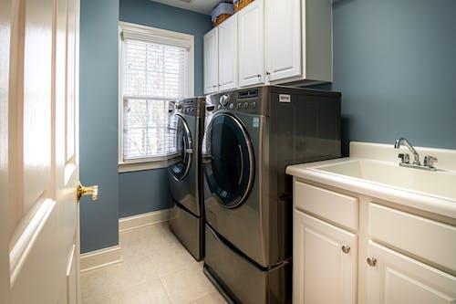 Front Load Washing Machine Beside White Window Blinds