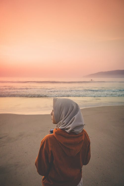 Person Wearing Headscarf Standing on Brown Sand Beach