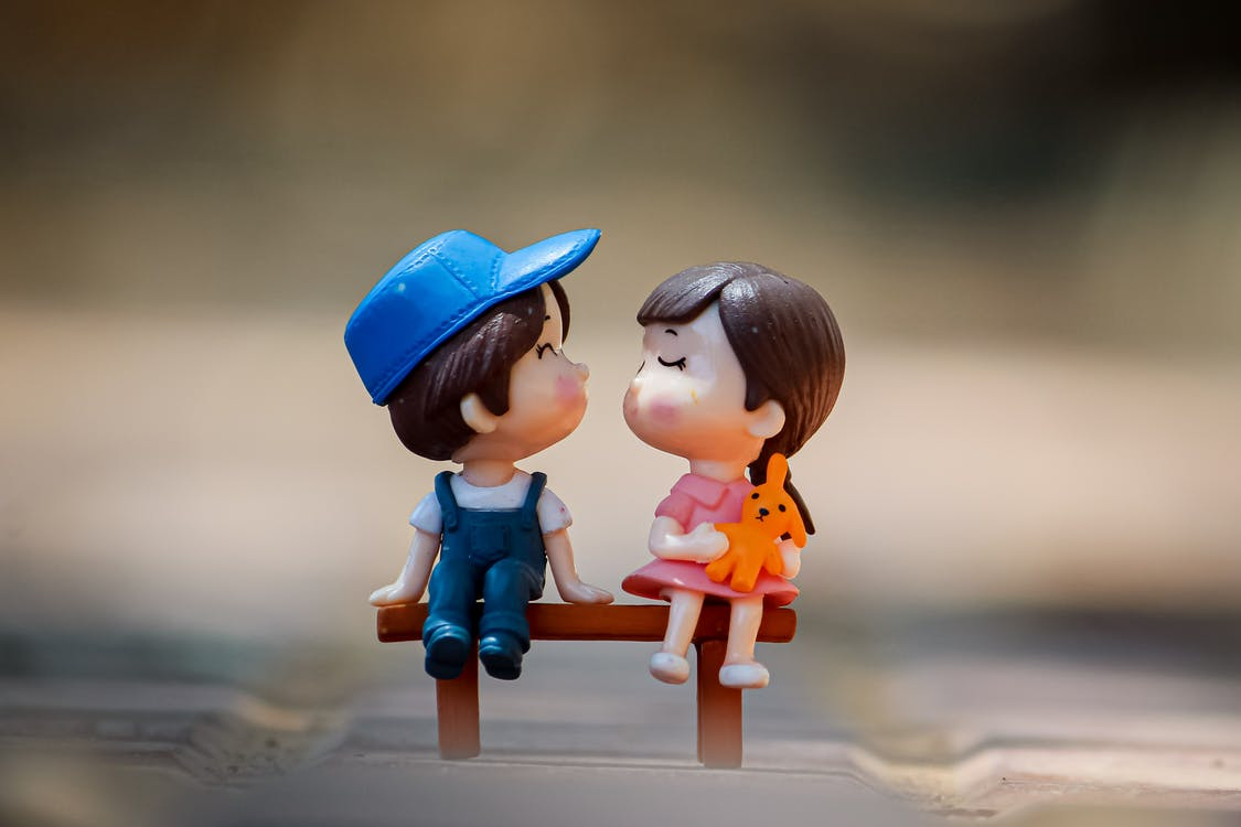 Tiny figurine of cute little girl and boy sitting on bench together and kissing