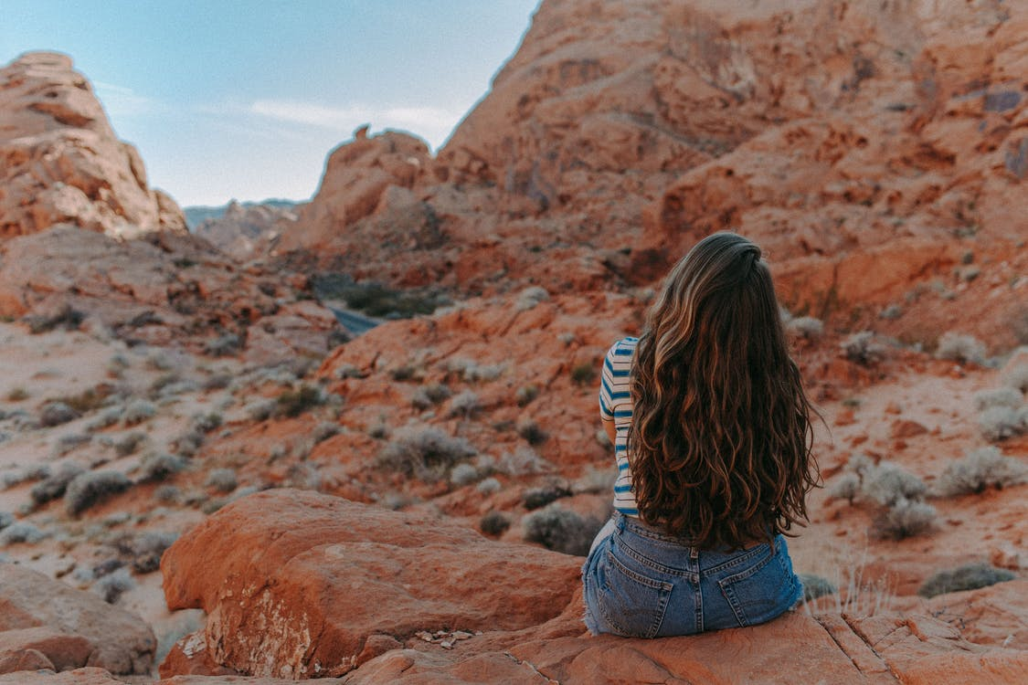 Woman in Blue Denim Shorts Sitting on Brown Rock Mountain