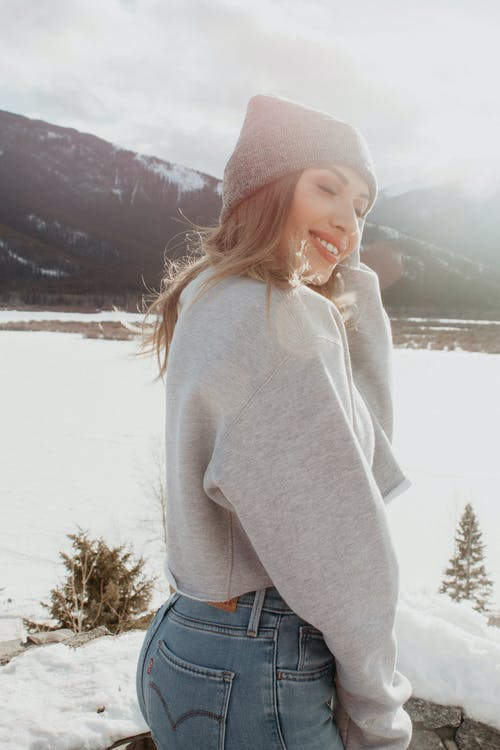 Woman in Gray Sweater and Blue Denim Jeans Standing on Snow Covered Ground