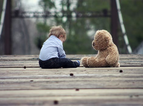 Boy Sitting With Brown Bear Plush Toy on Selective Focus Photo