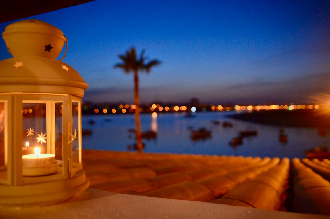 Selective Focus of Candle Lantern Near Body of Water