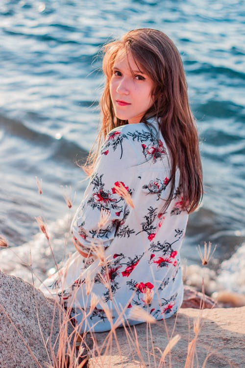 Woman In Floral Long Sleeve Shirt Sitting On A Rock Near Body Of Water
