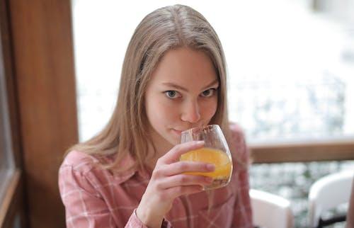 Woman in Pink Long Sleeve Shirt Drinking Orange Juice