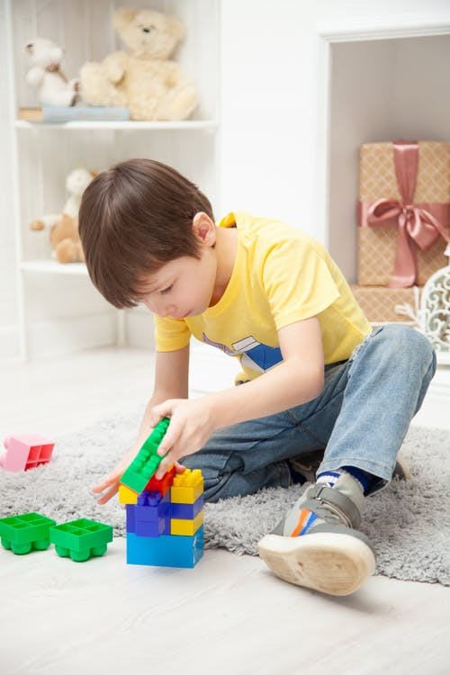 Boy In Yellow T-shirt And Blue Denim Jeans Playing With Plastic Toys