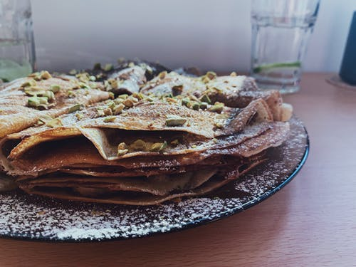 Tasty homemade pancakes with garnish placed on black plate near glass of water on wooden table
