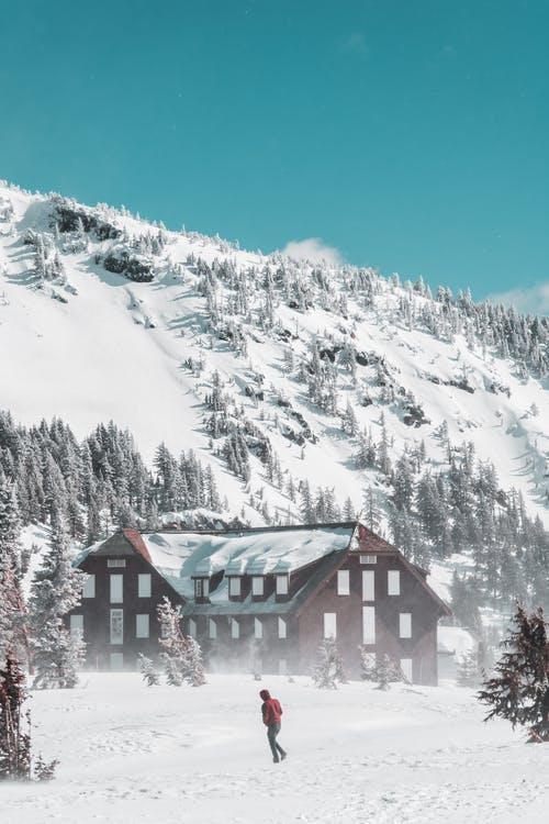 White and Brown House Near Snow Covered Mountain
