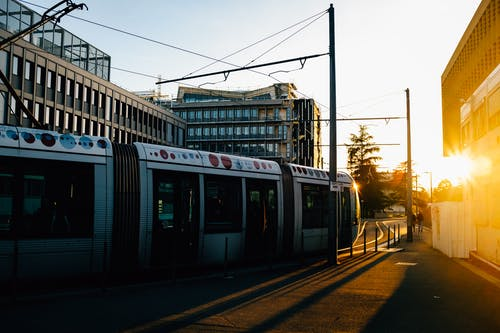 Tram riding on city street in evening time