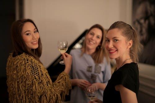 3 Women Smiling Holding Wine Glasses